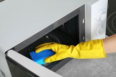 Woman cleaning microwave oven with sponge in kitchen royalty free stock photography