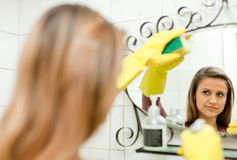 Woman cleaning mirror in bathroom royalty free stock photo