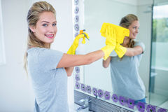 Woman cleaning the mirror. In the bathroom royalty free stock photo