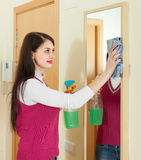 Woman cleaning  mirror  with cleanser Stock Image