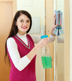 Woman cleaning  mirror  with cleanser Royalty Free Stock Images