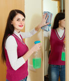 Woman cleaning  mirror  with detergent at home Stock Photo