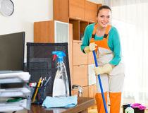 Woman cleaning office room. Smiling young cleaning woman washing the floor at office room Royalty Free Stock Images