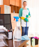 Woman cleaning at the office. Smiling female professional cleaner standing with cleaning equipment in office Stock Photo