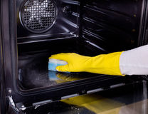 Woman cleaning oven. Close up of female hand with yellow protective gloves cleaning oven Royalty Free Stock Photo