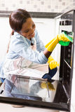 Woman cleaning oven. Happy african woman cleaning oven in the kitchen stock photography