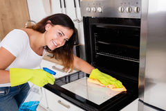 Woman Cleaning The Oven In Kitchen. Young Happy Woman Cleaning The Glass Door Of Oven In Kitchen royalty free stock photos