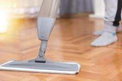 Woman cleaning parquet floor at home washing a mop royalty free stock photography