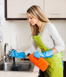 Woman  cleaning pipe   in kitchen Royalty Free Stock Images