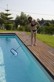 Woman cleaning the pool Royalty Free Stock Images
