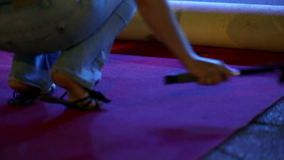 Woman is cleaning the red carpet squating in her jeans stock video