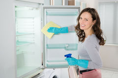 Woman Cleaning Refrigerator With Rag. Young Woman Cleaning Refrigerator With Rag At Home Royalty Free Stock Photos