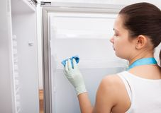 Woman cleaning refrigerator Royalty Free Stock Image