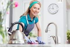 Woman cleaning in rubber gloves. Beautiful smiling woman in apron and rubber gloves cleaning kitchen countertop with pink wiping cloth stock images