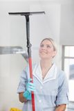 Woman cleaning with rubber window cleaner Royalty Free Stock Images