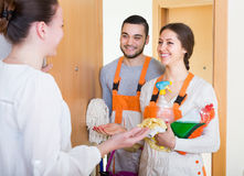 Woman and cleaning service workers. Housewife greeting cleaning service workers holding cleansers Stock Photography