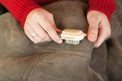 Woman cleaning a sheepskin with whisk broom Royalty Free Stock Images