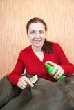Woman cleaning a sheepskin with whisk broom Royalty Free Stock Photos