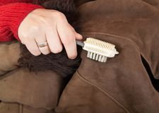 Woman cleaning a sheepskin with whisk broom Royalty Free Stock Photography
