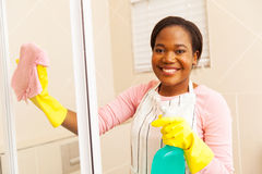 Woman cleaning shower door Royalty Free Stock Images