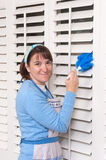 Woman cleaning shutters Stock Photos