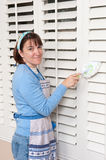 Woman cleaning shutters Stock Images