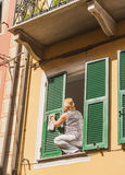 Woman cleaning shutters with great risk Stock Images