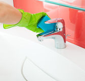 Woman cleaning sink and faucet Royalty Free Stock Images