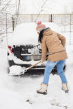 Woman cleaning snow around car Stock Images