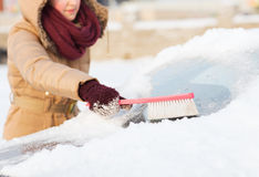 Woman cleaning snow from car back window Stock Image