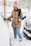 Woman cleaning snow from car Stock Image