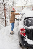 Woman cleaning snow car Stock Images