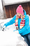 Woman cleaning snow car hood with scraper Royalty Free Stock Photography