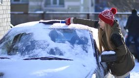 Woman cleaning snow from car roof using brush stock video