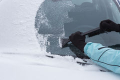 Woman cleaning snow from the car Royalty Free Stock Images