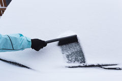 Woman cleaning snow from the car Royalty Free Stock Image