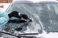 Woman cleaning snow from the car. In the winter Royalty Free Stock Photos
