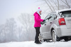 Woman cleaning snow from her car Royalty Free Stock Photo