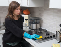 Woman cleaning stainless steel gas surface in  the kitchen at ho Royalty Free Stock Photo