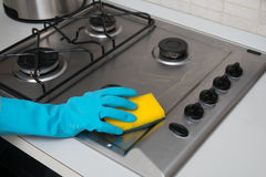Woman cleaning stainless steel gas surface in the kitchen at ho. Me royalty free stock photos