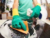 Woman cleaning stove in kitchen Stock Photos