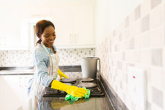 Woman cleaning stove Royalty Free Stock Images