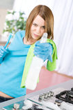 Woman cleaning stove with spray in kitchen Royalty Free Stock Photos