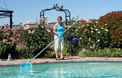 Woman cleaning swimming pool Royalty Free Stock Photography