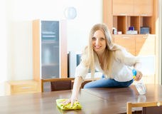 Woman cleaning  table with rag and cleanser Royalty Free Stock Image