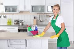 Woman cleaning table with rag. In kitchen royalty free stock photos
