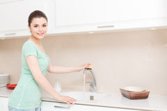 Woman cleaning tap in kitchen Royalty Free Stock Photo