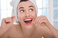 Woman cleaning teeth with floss Royalty Free Stock Photography