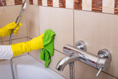 Woman cleaning tiles in bathroom Royalty Free Stock Images