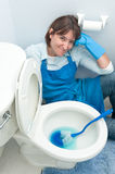 Woman cleaning toilet Stock Image